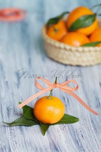 One mandarin on the leafs. Basket is on the background – Stock photos from around the world