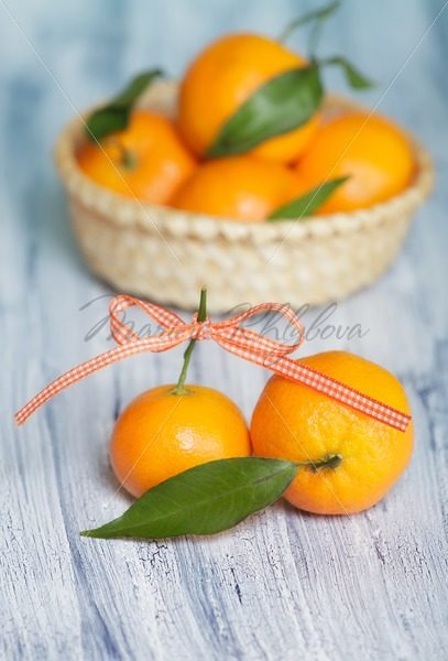 Two mandarins on the background of basket with mandarins – Stock photos from around the world