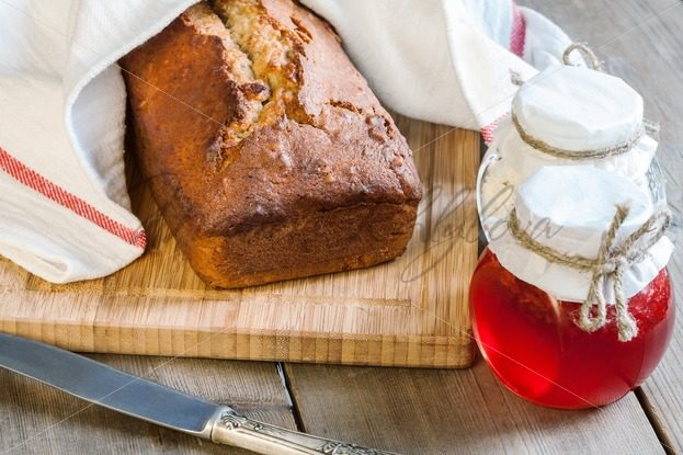 Banana bread covered with a dishcloth on the cutting board – Stock photos from around the world