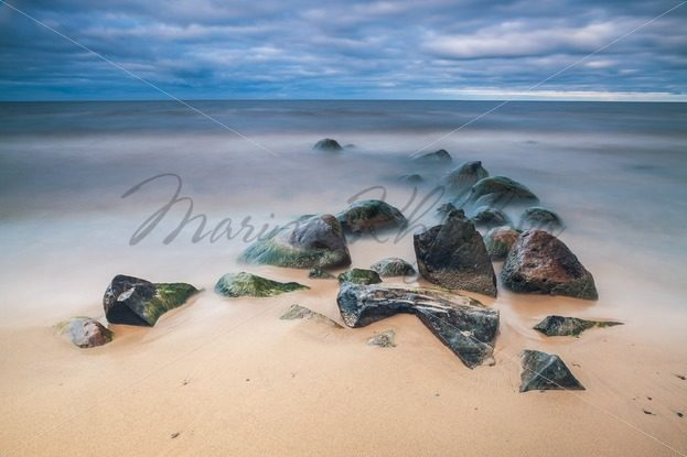 Wet stones on the sandy lake shore – Stock photos from around the world